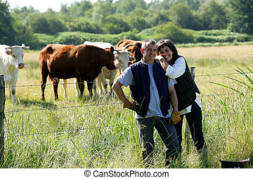 Farmer and wife stood in field of cows