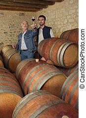 Two men tasting wine in cellar