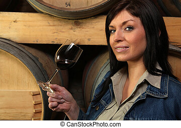 Woman tasting wine in a winery