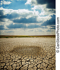 cracked earth under dramatic sky - last wet spot in cracked...