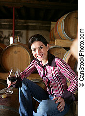Women in wine cellar with wine glass