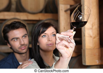 Couple examining a glass of red wine
