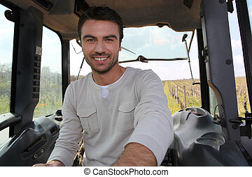 Smiling man driving tractor