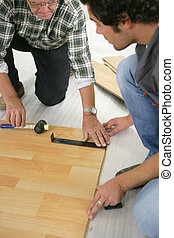 Father and son installing wooden flooring