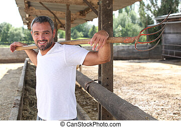 Farmer stood cleaning animal enclosure with pitch fork