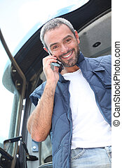 Farmer standing in the cab of his tractor talking on a cellphone