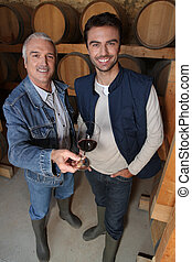 Smiling winegrowers in cellar
