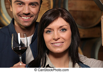 Couple drinking red wine in a cellar