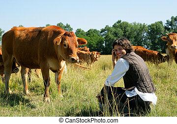 Farmer kneeling by cows in field