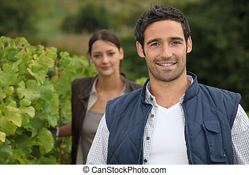 Young farmer stood with wife in vineyard