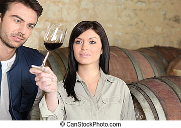 Couple in a cellar tasting wine