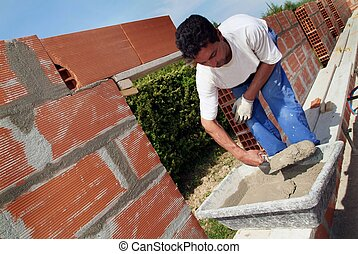 Mason constructing a wall alone