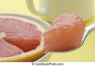 Grapefruit Bite - Grapefruit section on a spoon with half...