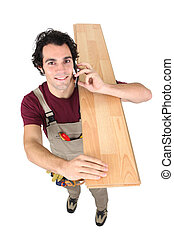 Manual worker carrying wooden plank