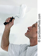 Decorator repainting ceiling