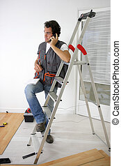 Man laying a floor and taking a phone call