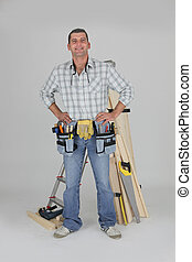portrait of carpenter fully equipped standing with arms...