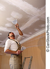 Plasterer working on ceiling