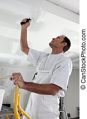 Man painting ceiling with roller