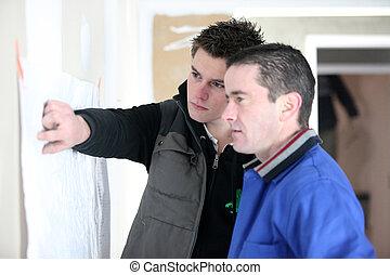 craftsmen looking at a plan