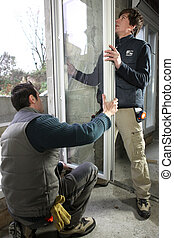 Two workers fitting window