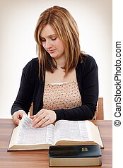 Searching for promises - Young christian woman turning pages...