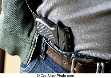 Pistol hidden in belt - Tucked in a belt pistol being...