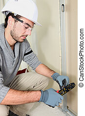 Man cutting electrical wire