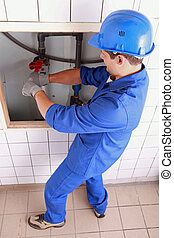 Plumber using a wrench on some large water pipes
