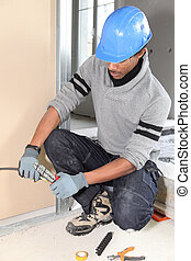 Electrician fixing wall electrics