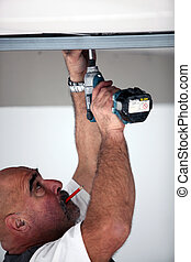 Man drilling into ceiling