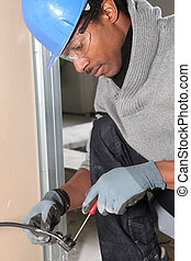 Afro-American laborer installing wiring