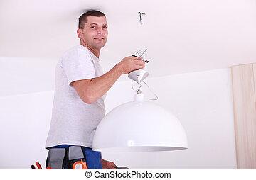 Man installing a ceiling light
