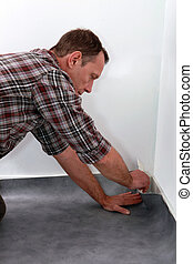 Man pushing lino flooring to fit into a corner
