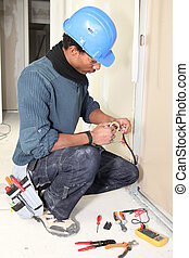 Electrician taping a wire