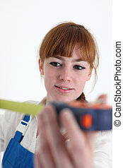 Woman using a measuring tape