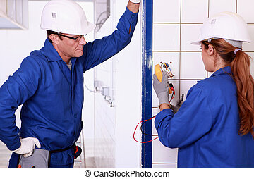 Male electrician supervising female apprentice