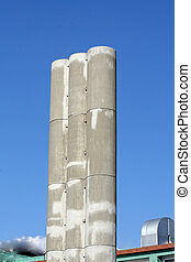 three high concrete chimney with a backdrop of sky