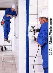 Tradesman using an electric screwdriver