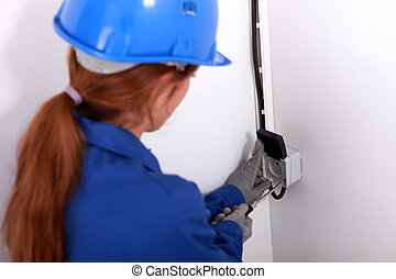 Young woman fitting an electrical socket