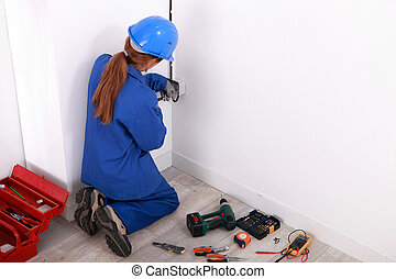 Female electrician installing a power point