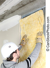 Man attaching insulation to wall