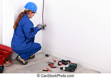 Young woman wiring a plug socket
