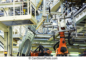 robots in a car factory - robotic arms in a car factory