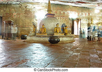 Ancient statues of Buddha around small stupa and painting on...