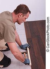 Carpenter installing parquet flooring