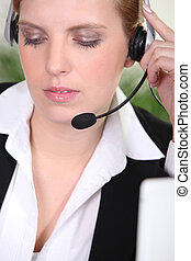 Closeup of a woman using a telephone headset