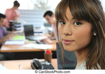 Young woman in a busy office
