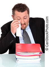 Businessman crying in front of stack of folders