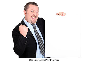 A successful businessman holding up a blank sign